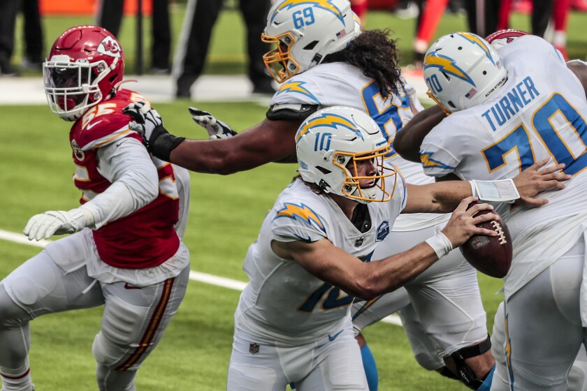 Chargers quarterback Justin Herbert scrambles against the Chiefs defense.