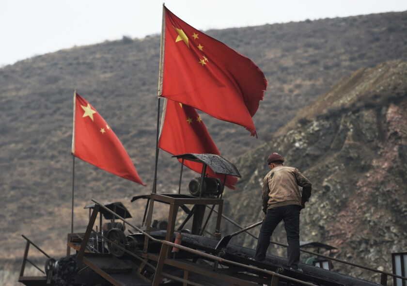 Chinese flags fly as a worker clears a conveyer belt near a coal mine at Datong, in China's northern Shanxi province, on Nov. 20, 2015.