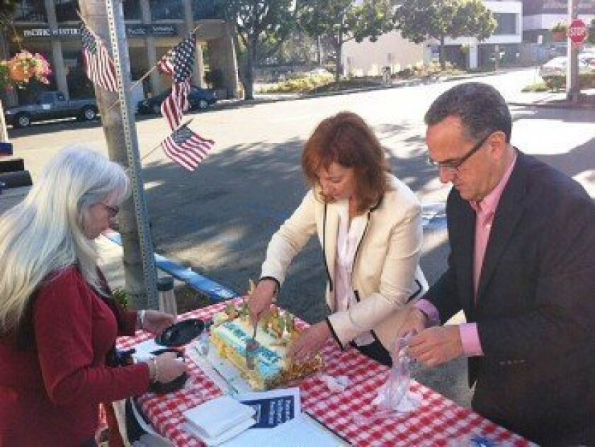 Post Office Task Force Chair Leslie Davis and Vice-Chair Joe LaCava serve cake to attendee Cathy Jones