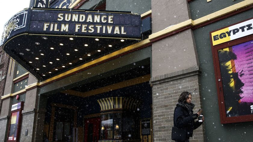 PARK CITY, UTAH - JANUARY 23: Snow falls as people walk past the Egyptian Theater with trucks lining