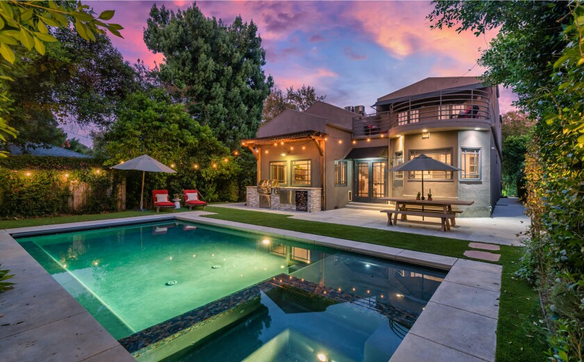 Exterior of home and a backyard area with a pool under string lights.