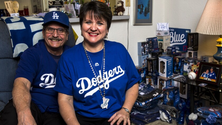 Dodgers fans Bill Snoberger and Mary Jones pose next to their Dodgers memorabilia.