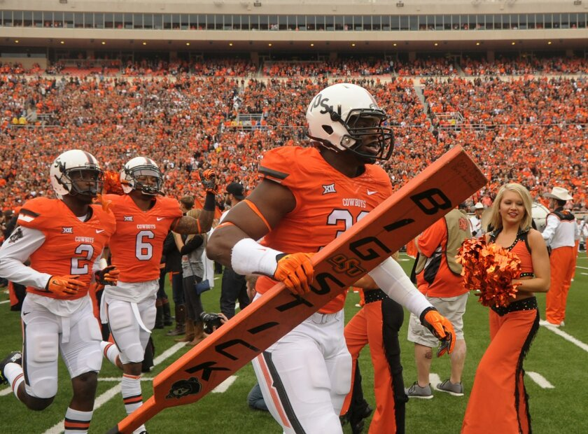 """FILE - In this Oct. 24, 2015, file photo, Oklahoma State defensive end Emmanuel Ogbah (38) carries the team's """"Big Stick"""" onto the field at the start of an NCAA college football game between Kansas and Oklahoma St in Stillwater, Okla. No. 5 TCU is at No. 12 Oklahoma State on Saturday, Nov. 7, 2015,"""
