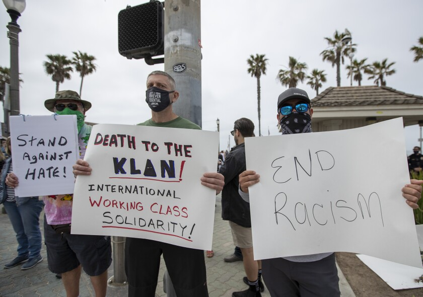 Nick McLachlan, Cliff Smith and Gesus Portilla hold signs during an antiracism rally in Huntington Beach.