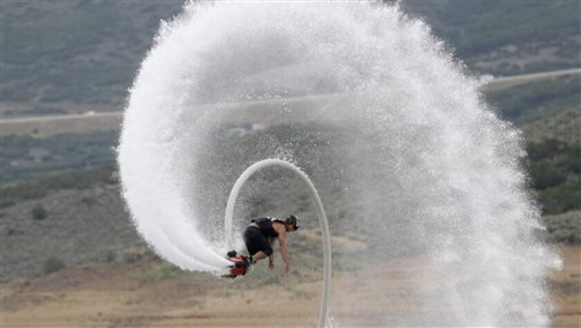 This July 24, 2013, photo, Rocky Mountain Flyboard instructor Chase Shaw flips with his flyboard, on the Jordanelle Reservoir, at Jordanelle State Park, Utah. The Flyboard, which looks like a small snowboard attached to a hose, can propel you 45 feet in the air using water pumped from a personal watercraft like a Jet Ski to the base of the board. New devices that pump water fast enough to make people defy gravity are drawing thrill-seekers eager to try the next new watersport, but Hawaii fisherm