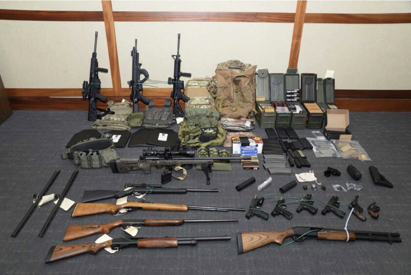 """FILE - This undated file image provided by the Maryland U.S. District Attorney's Office shows a photo of firearms and ammunition that was in the motion for detention pending trial in the case against Coast Guard lieutenant Christopher Hasson, accused of stockpiling guns and targeting Supreme Court justices, prominent Democrats and TV journalists. Hasson has asked a federal appeals court to let him withdraw his guilty plea or else throw out his sentence of more than 13 years in prison. In a court filing Monday, June 8, 2020 a defense attorney argued that Christopher Hasson's 160-month prison term was roughly four times longer than sentencing guidelines would have called for if U.S. District Judge George Hazel had not mistakenly applied a """"terrorism enhancement"""" to the sentence. (Maryland U.S. District Attorney's Office via AP, File)"""