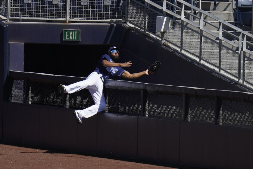 Tampa Bay Rays right fielder Manuel Margot reaches over a right field wall after catching a foul ball.