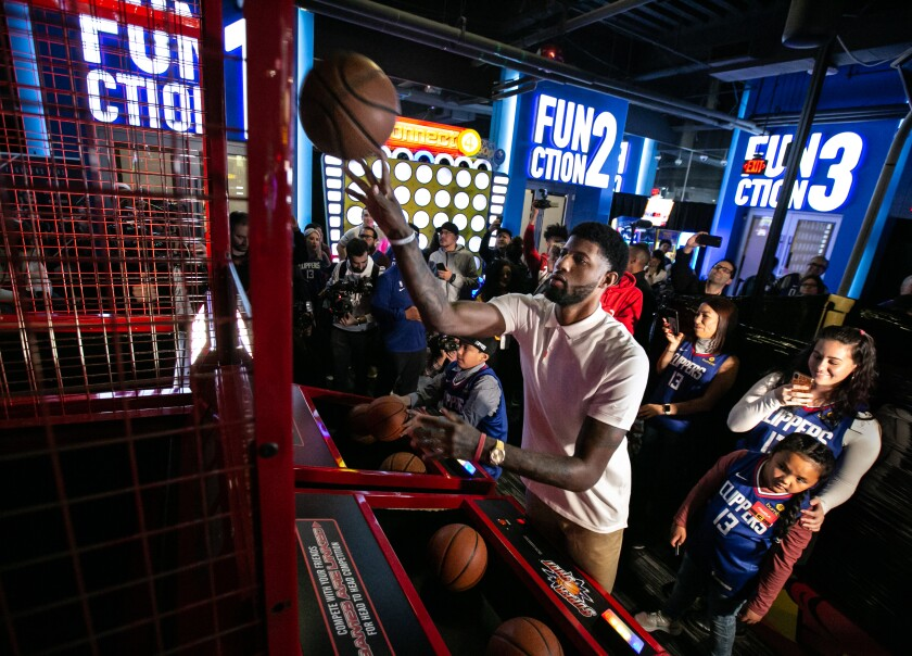 Clippers star Paul George shoots hoops with kids attending his third annual Christmas celebration at Dave & Buster's.