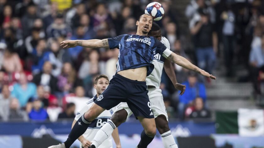 LA Galaxy's Zlatan Ibrahimovic, front, and Vancouver Whitecaps' Doneil Henry vie for the ball during