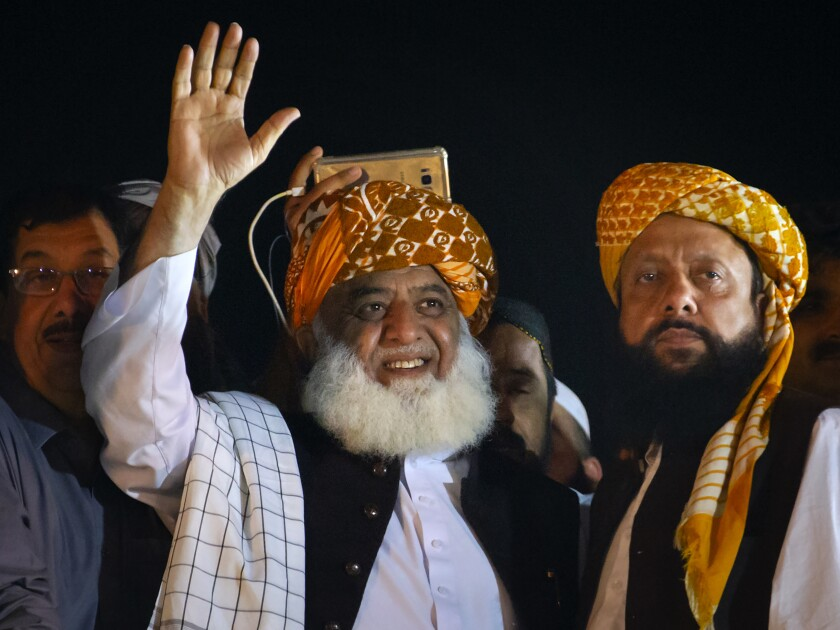 Firebrand cleric Maulana Fazlur Rehman, center, and head of the Jamiat Ulema-e-Islam party waves to his supporters during an anti-government march, in Islamabad, Pakistan, Sunday, Nov. 3, 2019. Tens of thousands of Islamists at a massive protest camp in Pakistan's capital awaited a deadline set by their leader calling for Prime Minister, Imran Khan to resign. (AP Photo/Anjum Naveed)