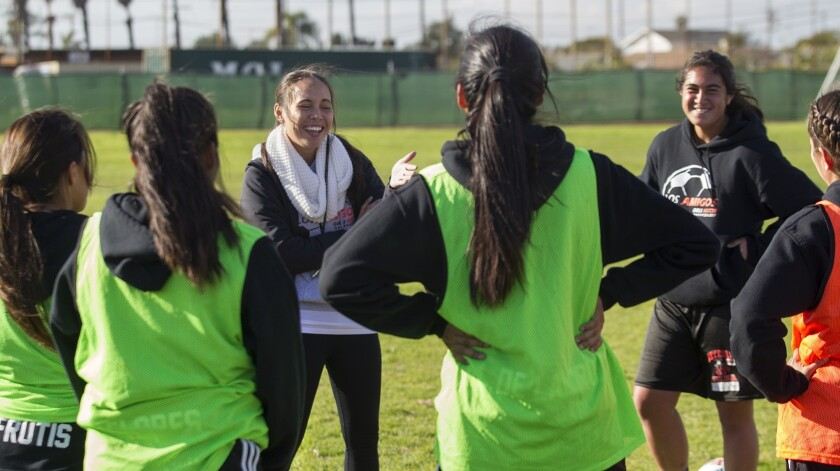 Los Amigos High Cassidy Abad, left, shares a laugh with her players during a team practice on Tuesda