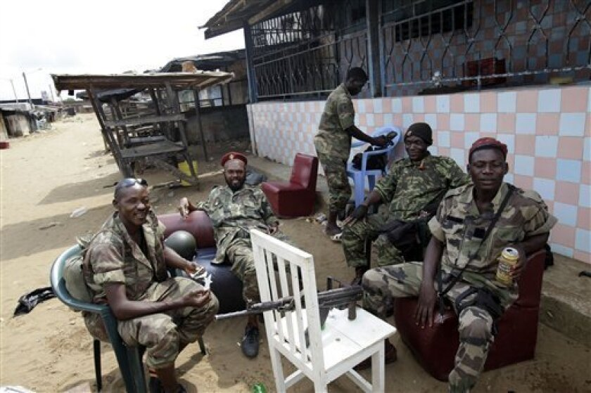 Soldiers loyal to Alassane Ouattara relax in a largely-deserted area of the Youpougon neighborhood, adjacent to a checkpoint serving as an operating base, at one of the main entrances to Abidjan, Ivory Coast, Thursday, April 7, 2011. Heavy arms fire rang out Wednesday near the home of the country's strongman who remained holed up in a subterranean bunker, as forces backing his rival assaulted the residence to try to force him out, diplomats and witnesses said.(AP Photo/Rebecca Blackwell)