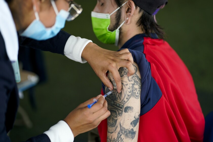 Una trabajadora de salud administra una dosis de la vacuna de Pfizer contra el COVID-19 durante la campaña de vacunación para personas de 18 a 29 años, el jueves 19 de agosto de 2021, en la Ciudad de México. (AP Foto/Eduardo Verdugo)