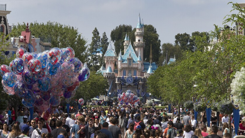 A large crowd strolls down Main Street, U.S.A., at Disneyland.