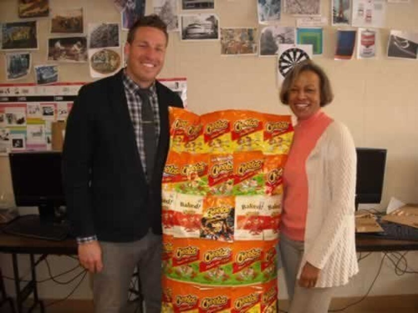 Art teachers Barak Smith and Barbara Gothard pose with a student project fashioned from recycled Cheetos bags.