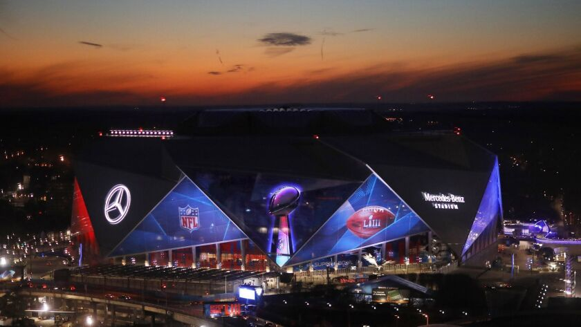 The sun sets behind Mercedes-Benz Stadium ahead of Sunday's NFL Super Bowl 53 football game between