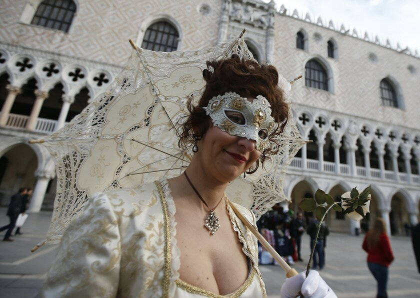 A masked woman walks prior to the Carnival Grand Opening show, in Venice, Italy, Saturday, Jan. 23, 2015. The Venice carnival in the historical lagoon city attracts people from around the world. (AP Photo/Luca Bruno)
