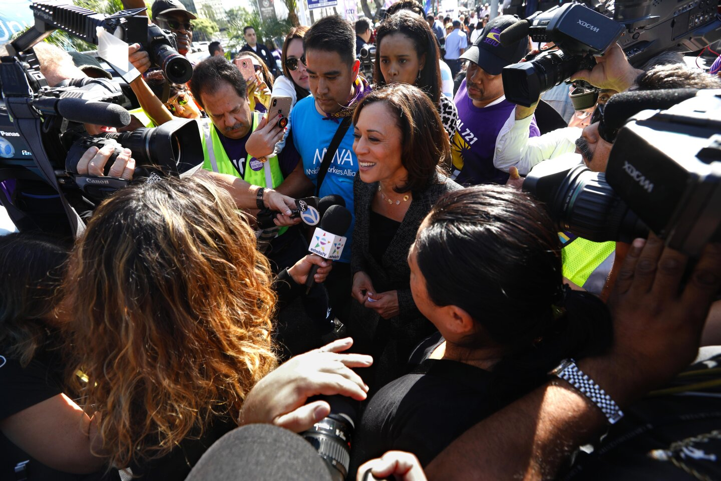 LOS ANGELES, CA - OCTOBER 2, 2019 - - Senator Kamala Harris, center, speaks to media after addressing hundreds of airport workers, Uber and Lyft drivers, janitors, city and county workers, and other workers before marching to Los Angeles International Airport in Los Angeles on October 2, 2019. The marchers are demanding that elected officials, locally, statewide and federally, take action to support unions for all people--no matter where they work. Workers also marched for better pay and benefits and want to unionize. The rally is on behalf of all kinds of workers, from rideshare to fast food to airport service workers. Speakers also included Los Angeles County Supervisor Janice Hahn, former state Sen. Kevin de Leon and Mary Kay Henry, president of the Service Employees International Union. The Rev. Jesse Jackson was also in attendance. (Genaro Molina / Los Angeles Times)