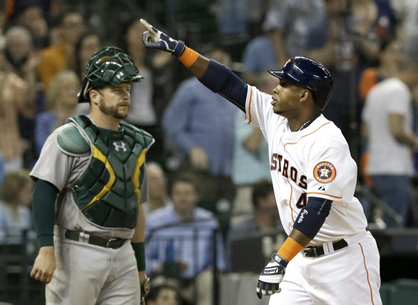 Houston Astros' Luis Valbuena, right, points to the stands after crossing the plate on a solo home run as Oakland Athletics catcher Stephen Vogt looks to the mound in the seventh inning of a baseball game Wednesday, April 15, 2015, in Houston. (AP Photo/Pat Sullivan)
