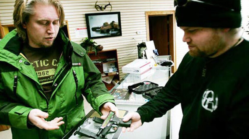 "Eric Thompson shows a handgun to customer Nicholas Koch in his Green Bay, Wis., showroom. Koch, a regular customer and former Marine who has six or seven handguns at home, says he resents the blame Thompson receives for his customers' crimes: ""It's like Chevy getting blamed for people driving drunk."""