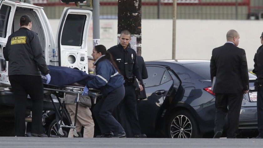 Los Angeles County coroner's investigators remove a man's body from a bullet-riddled car with an Uber sticker near the intersection of Griffin Avenue and North Broadway on Tuesday morning.