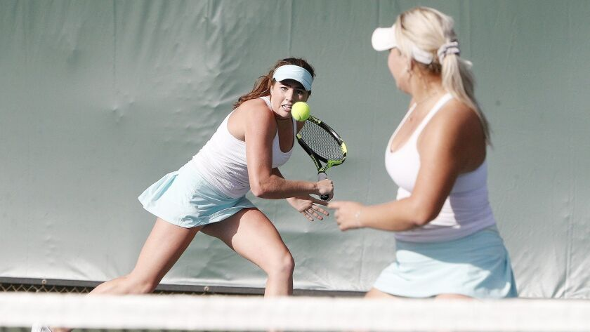 Corona del Mar's Roxy Mackenzie chases down the ball for a backhand return in a doubles match with t