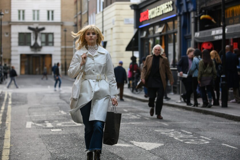 A woman in a long white coat walks down a street carrying a bag while a white haired man follows her.
