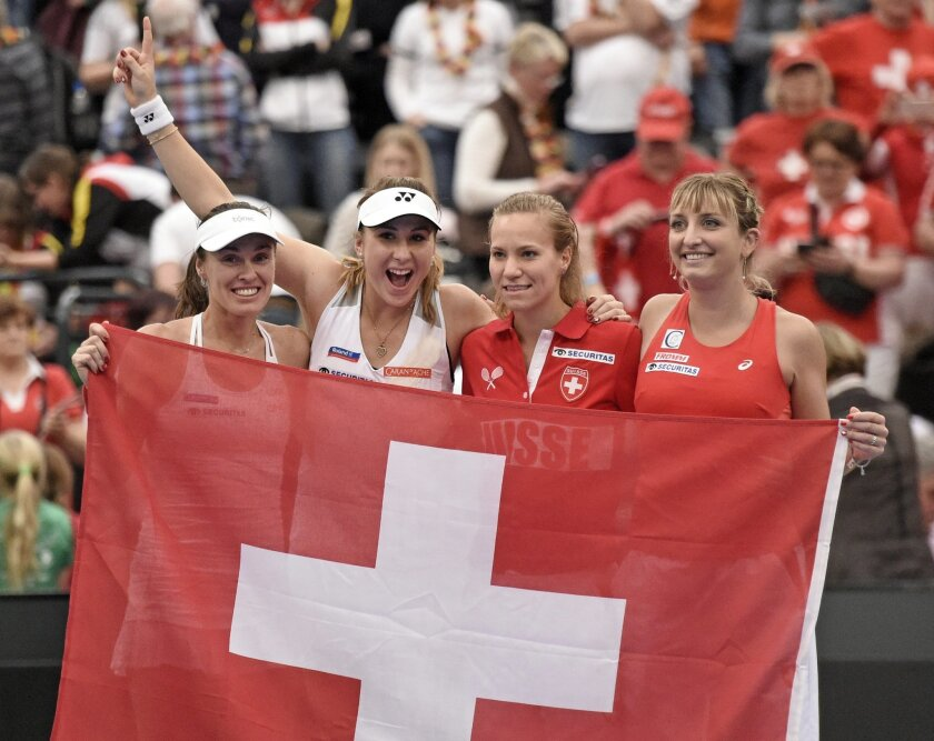 Martina Hingis, Belinda Bencic, Viktorija Golubic, Timea Bacsinszky, from left to right, of Switzerland, celebrate after winning the Fed Cup World Group first round tennis match between Germany and Switzerland at the Leipzig Fair in Leipzig, Germany, Sunday, Feb. 7, 2016. (AP Photo/Jens Meyer)