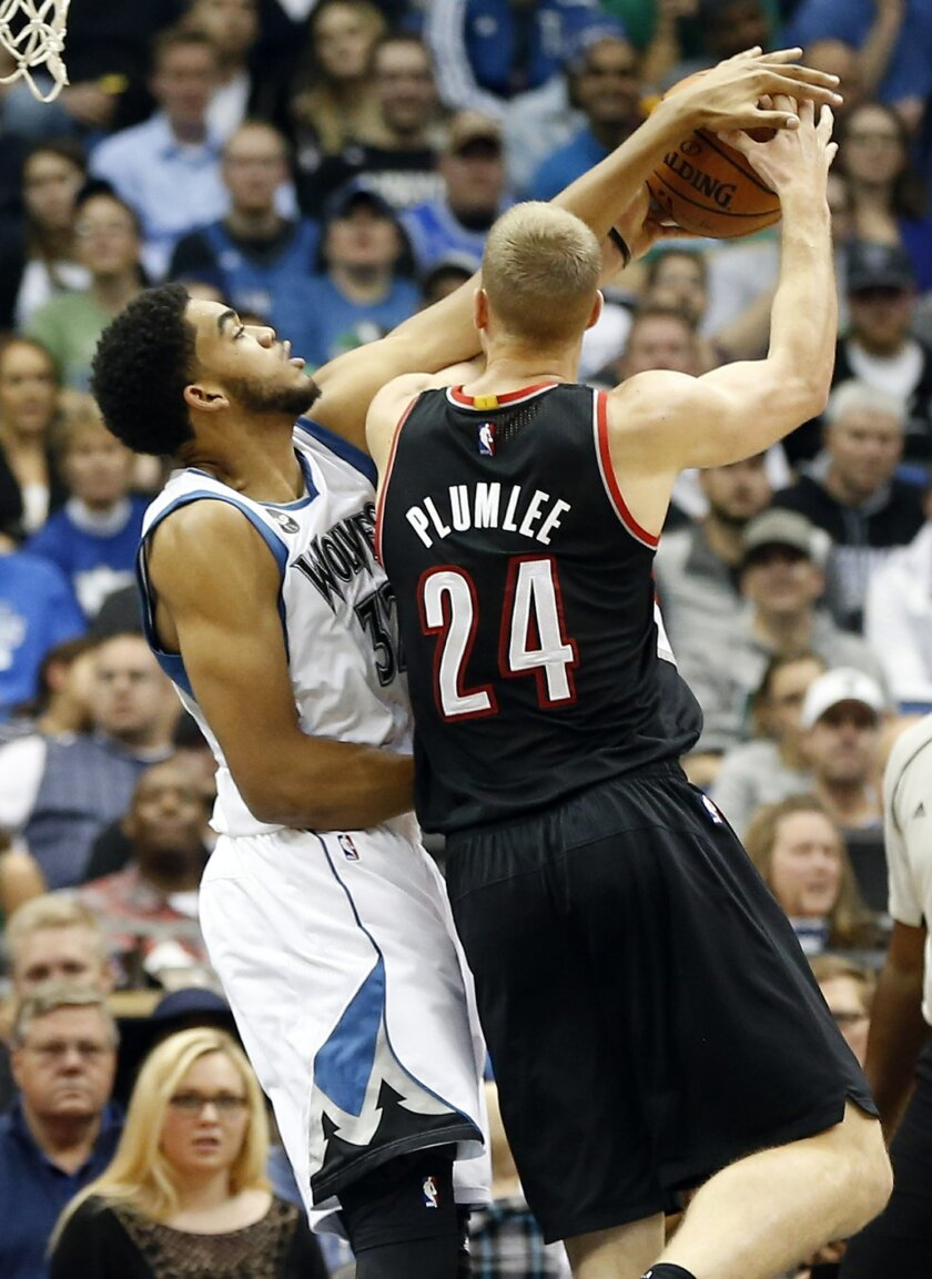 Minnesota Timberwolves' Andre Mille, left, tries to block a shot by Portland Trail Blazers' Mason Plumlee in the first half of an NBA basketball game Monday, Nov. 2, 2015, in Minneapolis. (AP Photo/Jim Mone)