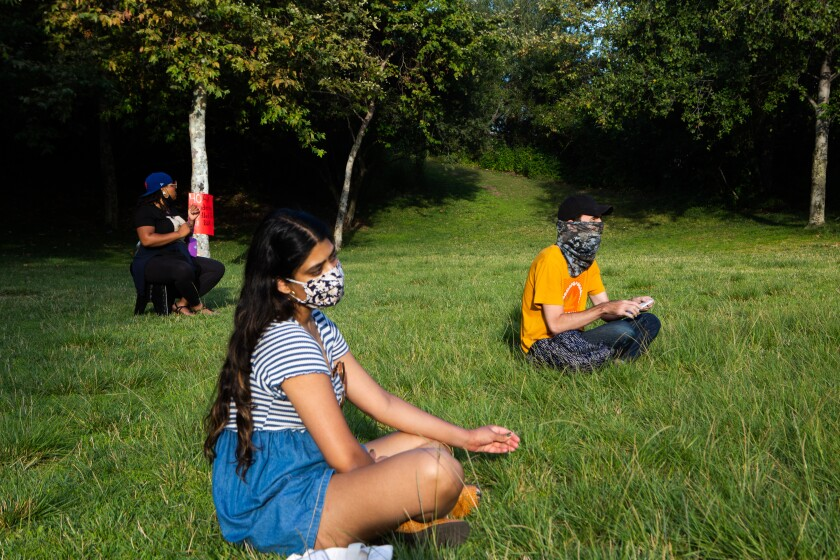 Parkgoers sit at a social distance in Vista Hermosa Natural Park on Tuesday.