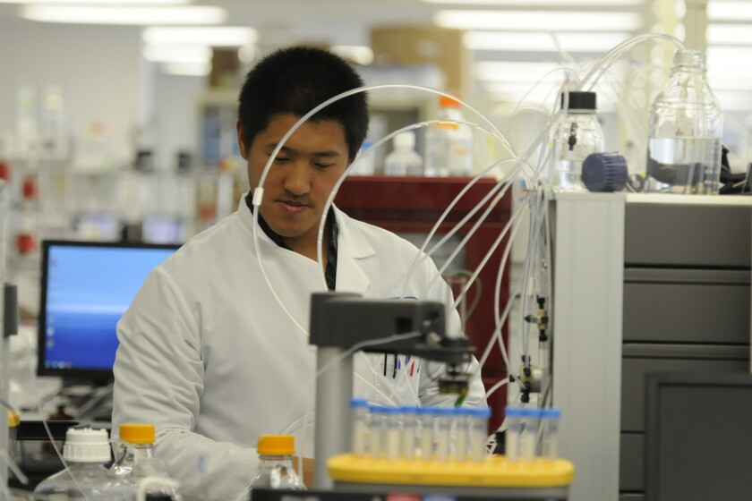 Protein Sciences scientist Guang Liu runs liquid through a purifying machine in Meriden, Conn.