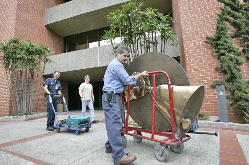 Bertin Porcayo wheeled away the Copley Newspapers logo after its removal from the Union-Tribune's Mission Valley headquarters Saturday. (Eduardo Contreras / Union-Tribune)