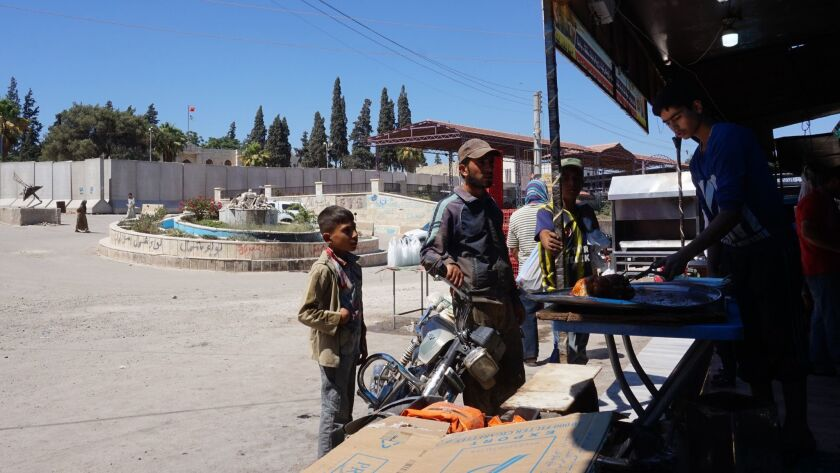 Locals purchase roasted chicken in central Afrin city. The roundabout used to have a monument to t