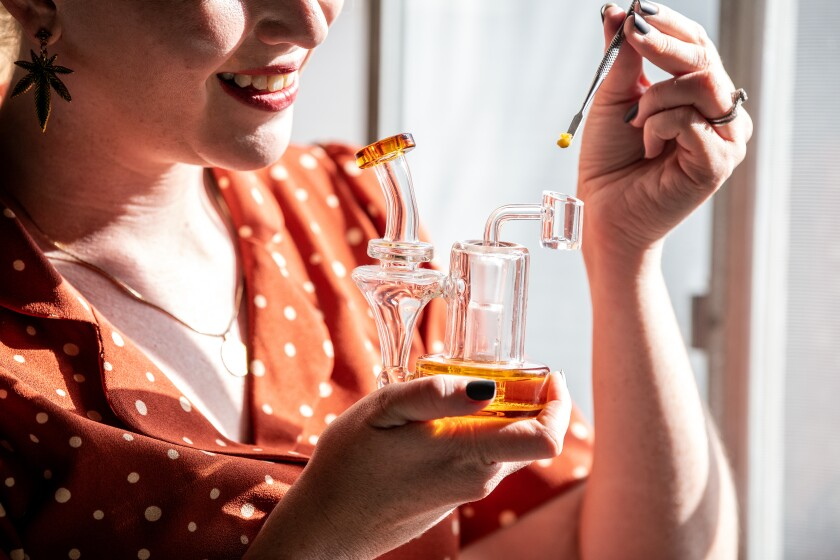 A woman holds a glass water pipe in one hand and a dab of THC concentrate in the other.