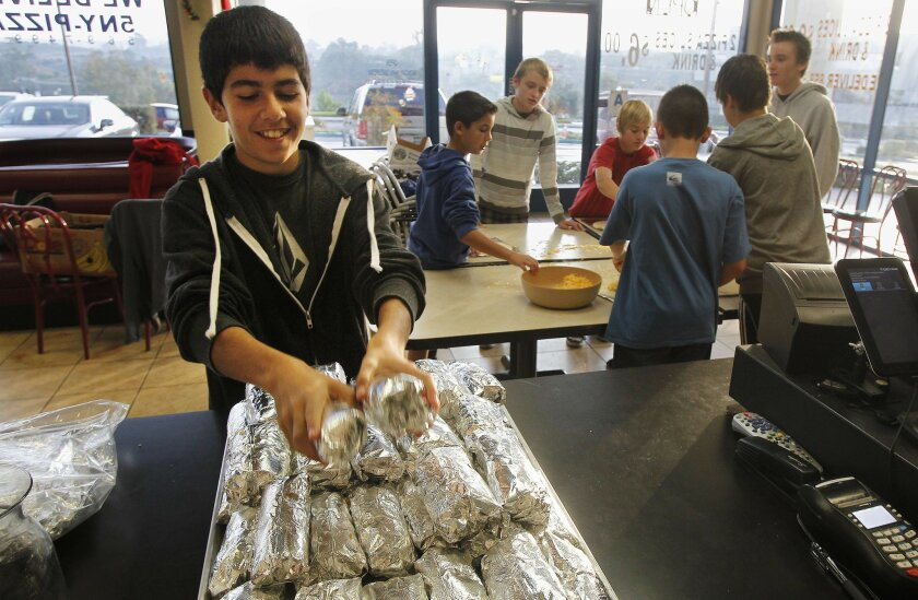 Alec Johnson, 13, stacks breakfast burritos at Long Island Mike's Pizza on a recent Sunday morning. Alec and his group of middle-school friends and parent volunteers have made more than 7,000 burritos for homeless people in downtown San Diego.