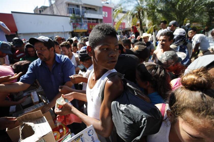 Migrantes hondureños reciben comestibles y se preparan para continuar su camino hoy, lunes 22 de octubre de 2018, en el jardín Hidalgo de Tapachula, en el estado de Chiapas (México). EFE