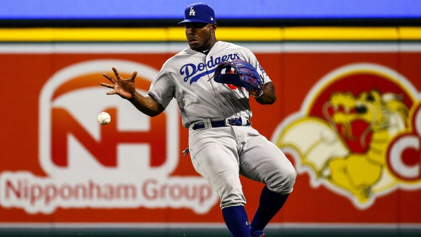 Dodgers right fielder Yasiel Puig (66) reaches to grab a hit to right field by Angels second baseman Ian Kinsler (3) late in the ninth inning.