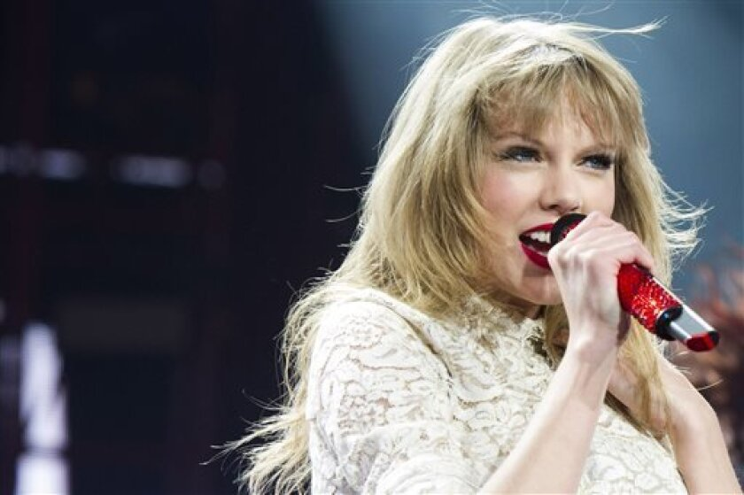 FILE - This March 29, 2013 file photo shows Taylor Swift performing at the Prudential Center in Newark, N.J. Billboard announced Wednesday, April 3, that Swift, Justin Bieber, Bruno Mars and R&B singer Miguel will perform at the Billboard Music Awards on May 19 in Las Vegas. (Photo by Charles Sykes/Invision/AP, file)