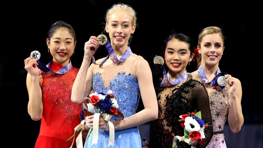 Bradie Tennell, in blue, is joined on the podium by, from left, silver medalist Mirai Nagasu, bronze medalist Karen Chen and fourth-place finisher Ashley Wagner at the U.S. figure skating championships on Friday night.