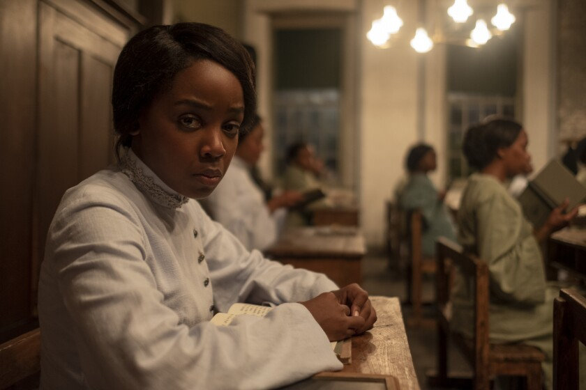 Thuso Mbedu sits at a desk with a book and looks at the camera.
