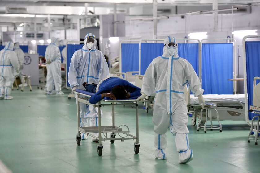 Medical professionals in PPE coveralls move a suspected coronavirus patient in New Delhi.