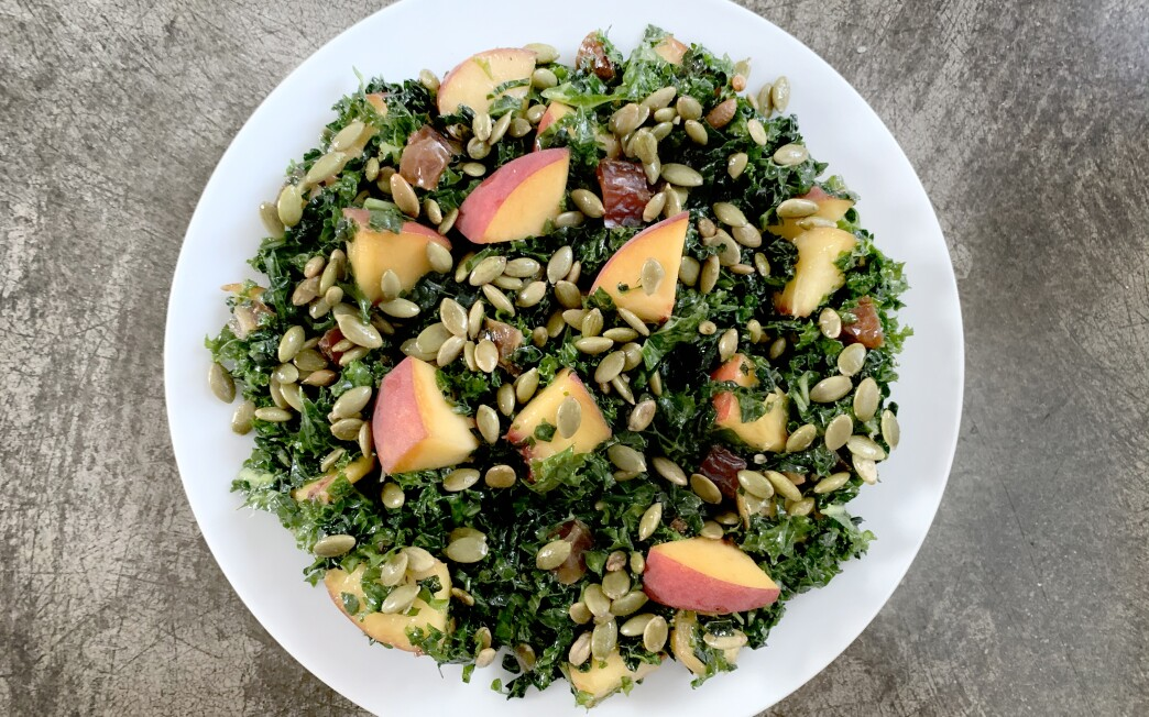 Kale salad with peaches and pepitas.