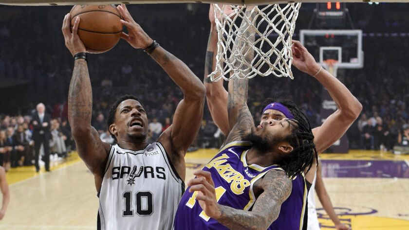 Lakers forward Brandon Ingram tries to block a shot by Spurs guard DeMar DeRozan during the first half Wednesday night.