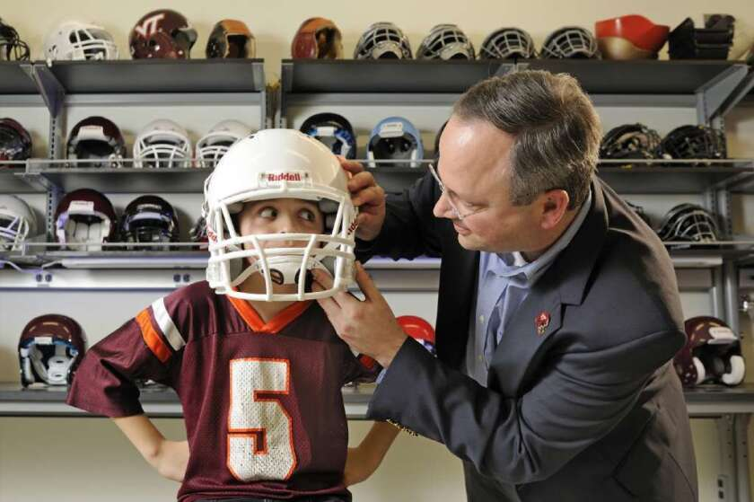 Another reason to stay in school longer: a new study finds that more education is associated with better outcomes following traumatic brain injury. Here, Virginia Tech concussion researcher Stefan Duma fits his son, Brock, with a football helmet.