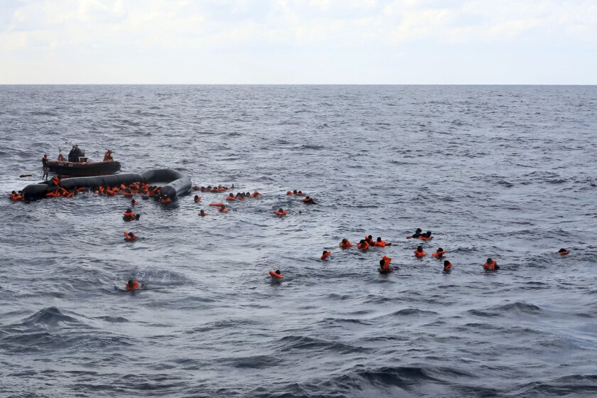 Refugees and migrants are rescued by members of the Spanish NGO Proactiva Open Arms, after leaving Libya trying to reach European soil aboard an overcrowded rubber boat in the Mediterranean sea, Wednesday, Nov. 11, 2020. The Open Arms rescue ship had been searching for the boat in distress for hours before finally finding it Wednesday morning in international waters north of Libya. The NGO had just finished distributing life vests and masks to the passengers to begin transferring them to safety when the flimsy boat split in half throwing them into cold waters. (AP Photo/Sergi Camara)
