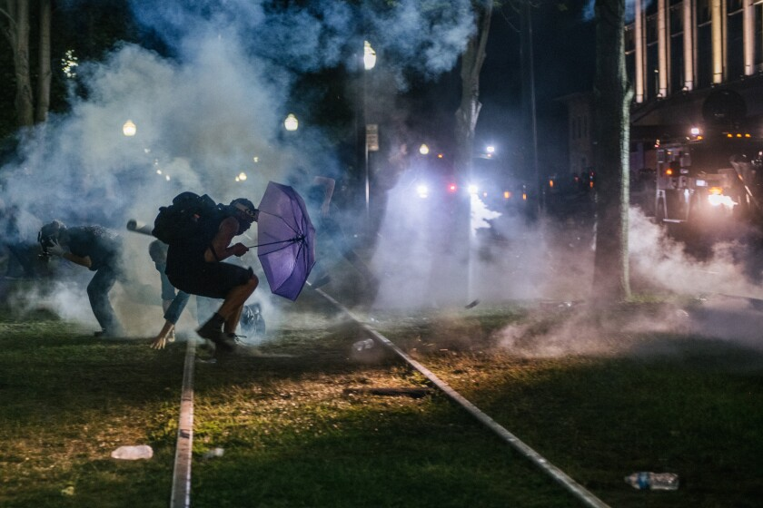 KENOSHA, WI - AUGUST 24: Demonstrators retreat from tear gas in front of the Kenosha County Courthouse on August 24, 2020 in Kenosha, Wisconsin. Additional law enforcement were deployed to protect the courthouse. Civil unrest occurred after the shooting of Jacob Blake, 29, on August 23. Blake was shot multiple times in the back by Wisconsin police officers after attempting to enter into the drivers side of a vehicle. (Photo by Brandon Bell/Getty Images)