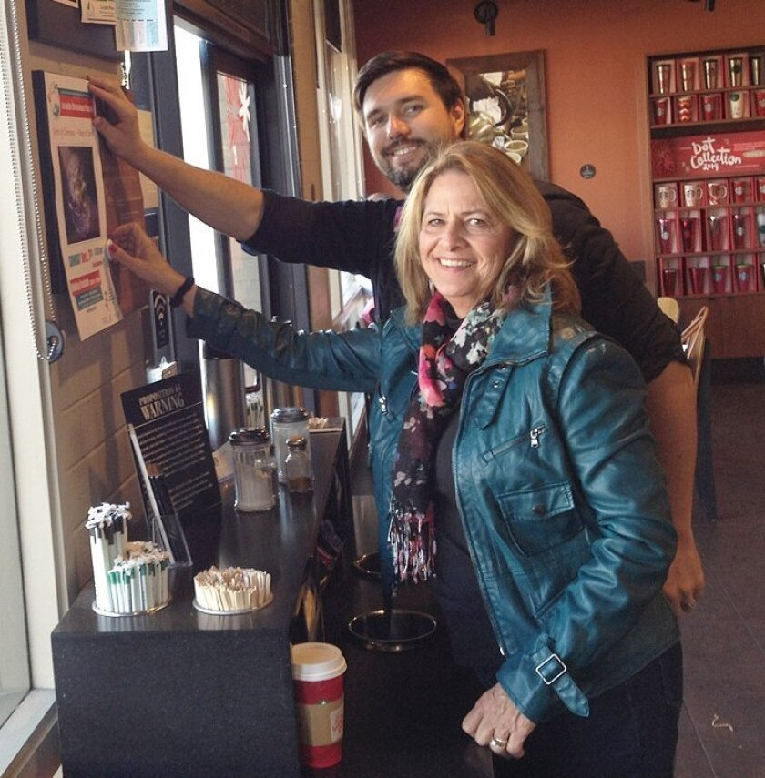 Christmas Parade Foundation President Ann Kerr Bach and Starbucks manager Jeremiah Briggs display a poster for this year's event.