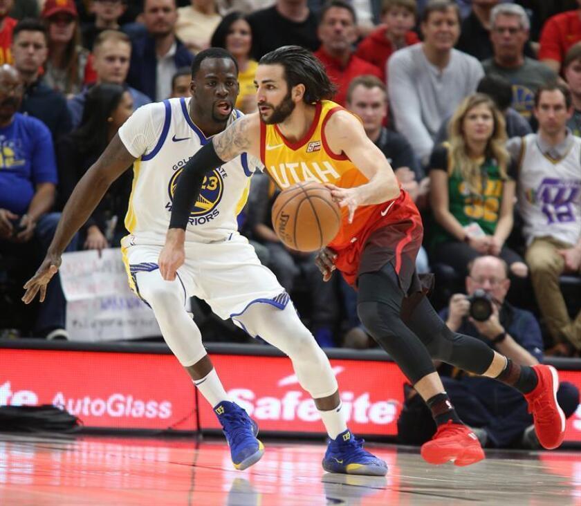 El defensa español Ricky Rubio (d) de los Utah Jazz en acción ante el delantero Draymond Green (i) de los Golden State Warriors durante el partido de la NBA entre los Utah Jazz y los Golden State Warriors que se disputa este martes 30 de enero de 2018, en el Energy Solutions Arena de Salt Lake City, Utah (EE.UU.). EFE