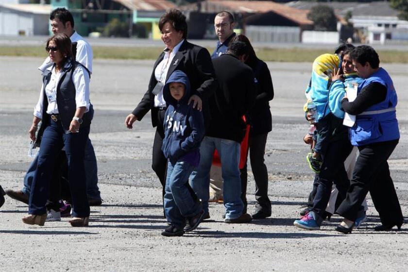 Catorce personas, cuatro madres y 10 niños deportados de Estados Unidos hacia Guatemala, caminan por la pista del aeropuerto internacional La Aurora de Guatemala. EFE/Archivo