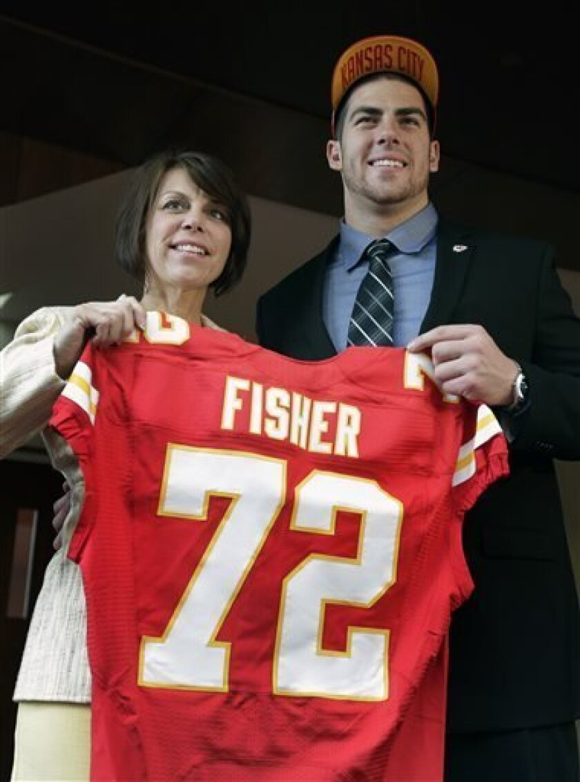 Kansas City Chiefs No. 1 draft pick Eric Fisher, an offensive lineman from Central Michigan, poses with his mother Heidi Langegger, during an NFL football news conference Friday, April 26, 2013, in Kansas City, Mo. Fisher was the No. 1 overall pick in the NFL draft on Thursday. (AP Photo/Charlie Ri